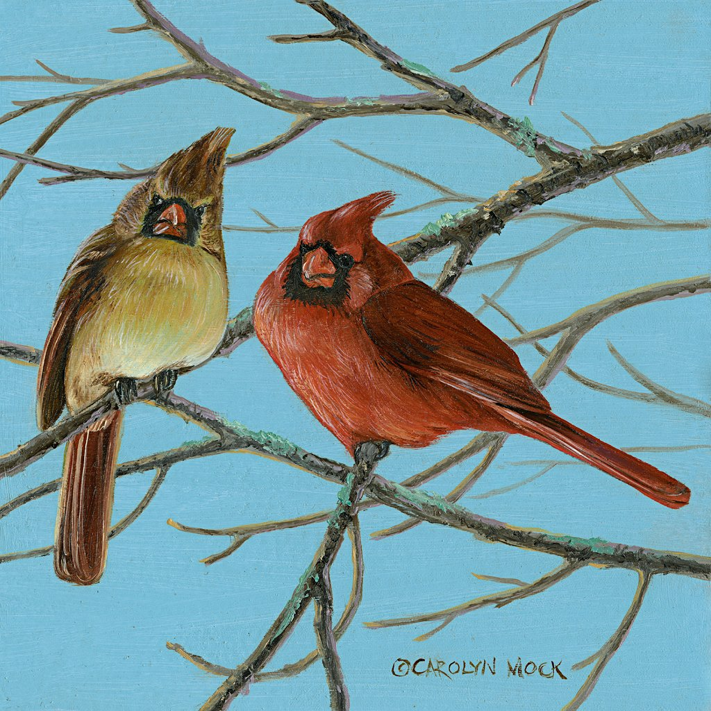 Two cardinals perched on a tree branch in the clear blue sky